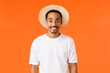 Leinwandbild Motiv Ready for vacation. Happy smiling african-american man wearing hat and t-shirt, travelling feeling upbeat finally relax by sea enjoy summertime, standing orange background
