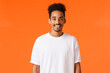 Leinwandbild Motiv Cheerful young hipster african american guy with moustache and afro haircut, wearing white t-shirt, smiling cute looking camera happy, standing orange background express positivity