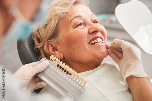 Fototapeta Dentist picking up shade using tooth enamel scale
