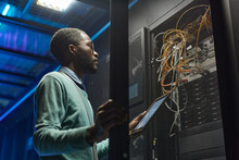 Low Angle Portrait Of African American Data Engineer Holding Digital Tablet While Working With Supercomputer In Server Room Lit By Blue Light, Copy Space