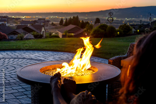 Fotografie, Obraz A woman relaxes by a roaring firepit on a paver patio at sunset overlooking the