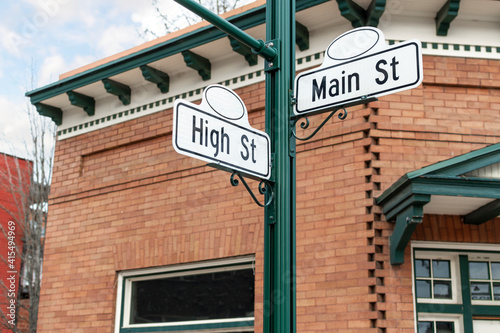 Fototapeta A vintage or retro street sign for High and Main streets in front of a turn of t