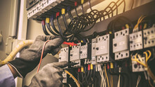 Close-up Hand Of Electrical Engineering Using Measuring Equipment Tool To Checking Electricity At Circuit Breaker And Cable Wiring System For Maintenance In Main Power Distribution Board.