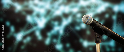 Fotografia Public speaking backgrounds, Close-up the microphone on stand for speaker speech presentation stage performance with blur and bokeh light background