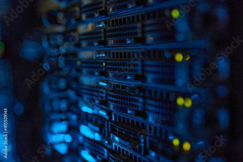 Futuristic background image of rack server with blinking lights in supercomputer, copy space