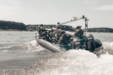 Group Of Military Fighters On A Boat With A Flasher Are Chasing Pirates. The Concept Of Sea Robberies, Piracy, Poaching.