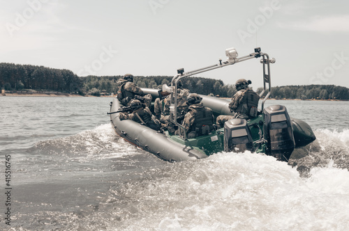 Fotografija Group of military fighters on a boat with a flasher are chasing pirates