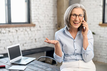 Excited Modern Senior Businesswoman Manager In Glasses And Casual Attire Standing In The Office, Taking Break To Call And Talk With Family, Holding Mobile Phone, Discussing News, Gossiping, Gesturing