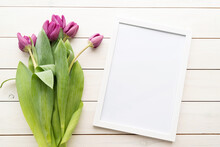 White Frame With Purple Spring Tulips Top View Over White Wooden Background