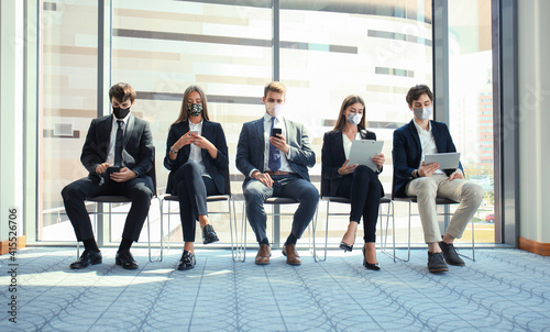 Fototapeta premium Stressful business people waiting for job interview with face mask, social distancing quarantine during COVID19 affect