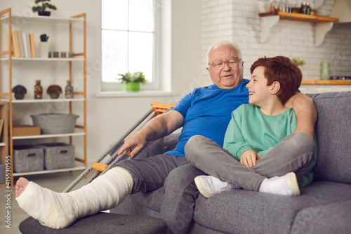 Little child helps, supports and takes good care of his grandpa with injury Fototapeta