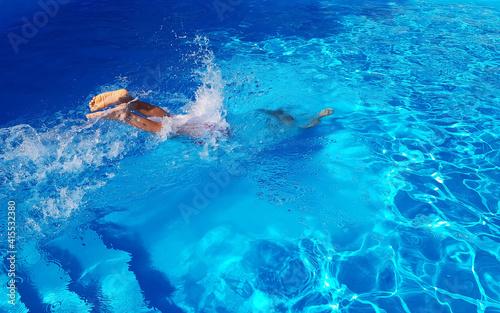 Fotografia man jumped into the blue pool