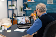 Old Parent Greenting Daughter During Video Conference On Portable Computer. Happy Grandfather Saying Hello In The Course Of Online Video Confencere With Family From Living Room.