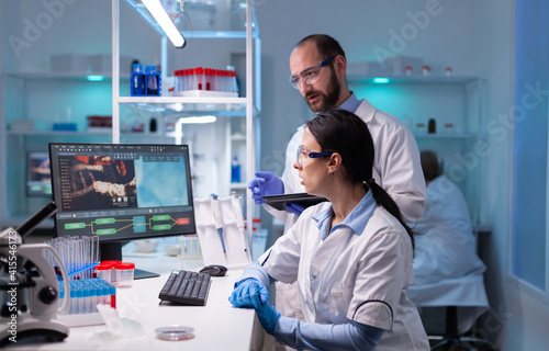 Fotografering Woman scientist and man doctor studying virus expertise in medicine lab working with professional technology equipment
