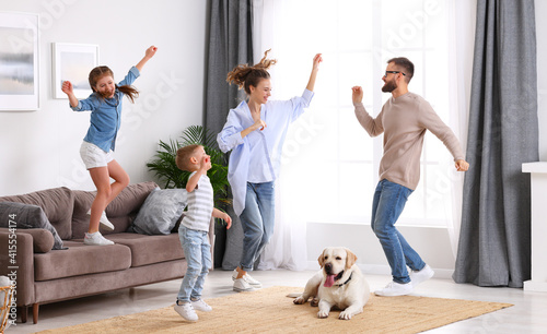 Playful family dancing in living room with dog #415554174