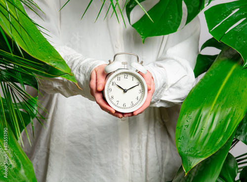 female hand holding alarm clock on background with palm leaves © Masson
