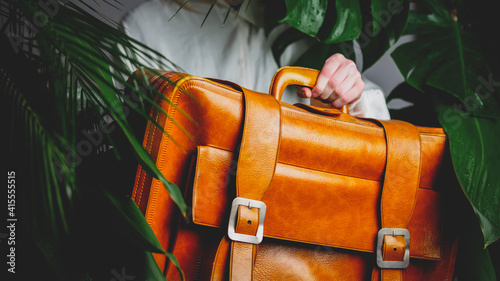 female hand holding suitcase on background with palm leaves © Masson