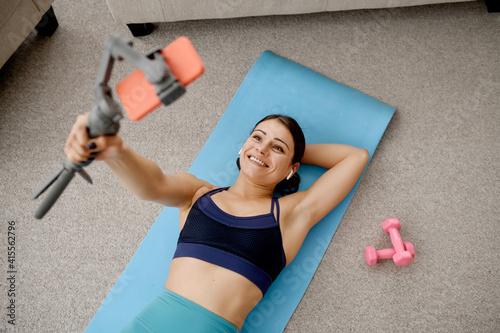 Fototapeta Woman lying on mat, online fit training with phone obraz