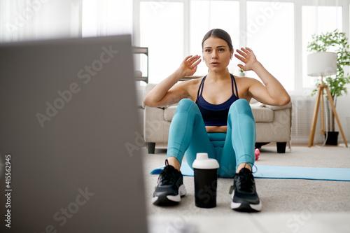 Fototapeta Woman sits on mat, online fitness training obraz