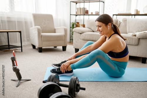 Fototapeta Girl sits on floor, online fitness training obraz
