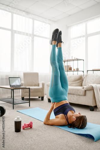 Fototapeta Girl doing exercise on press, online fit training obraz