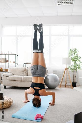 Fototapeta Woman stands upside down, online yoga training obraz