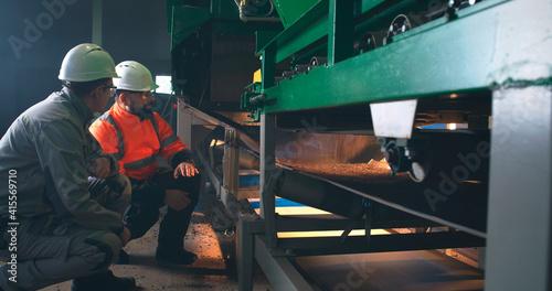 Slika na platnu Male colleagues discussing conveyor belt on factory