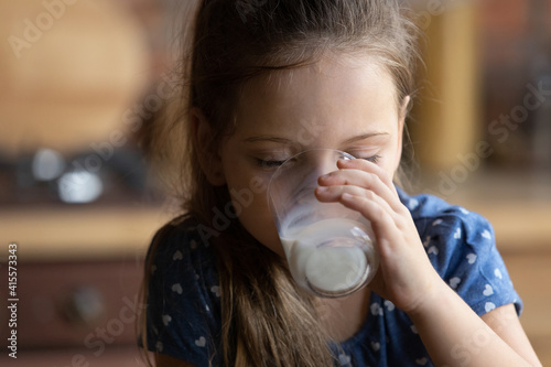 Obraz Close up cute little girl with closed eyes drinking tasty milk, pretty preschool child kid with closed eyes holding glass, enjoying organic food yogurt, getting vitamins and calcium, healthcare - fototapety do salonu