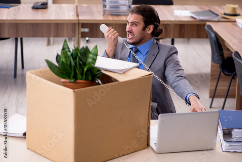 Fototapeta Young male employee being fired from his work