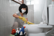 Housewife Wearing A Mask Wearing Gloves Brushing The Dirty Toilet In The Bathroom
