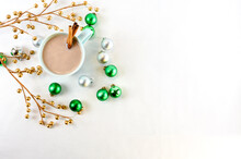 Hot Chocolate In Teal Mug With Christmas Ornaments On A White Background
