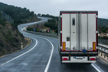 Refrigerated Truck Driving On A Conventional Road, With A Continuous Line And Many Curves.