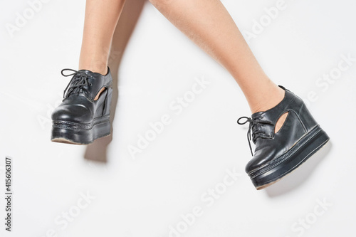 Fotomural Feet of a woman wearing black stylish leather boots with platforms on a brig bac