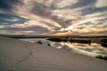 Ripples In Sand Dune With A Stick And Pond Of Water At Sunset
