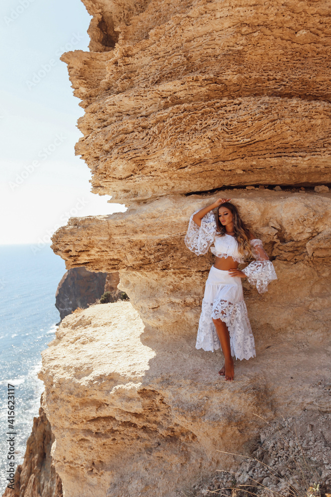 Fototapeta sexy woman with blond hair in elegant clothes and accessories posing on a cliff
