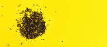 Loose Black Tea With Few Dried Flowers On Yellow Board, View From Above Space For Text Right Side