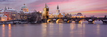 Panorama Of Snowy Charles Bridge At Sunset In Winter And Pink Colored Sky With Light In Prague In Czech Republic