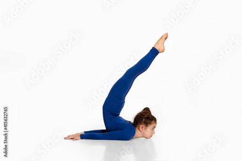 Foto flexible child girl in blue sportswear performs gymnastic exercises on white stu