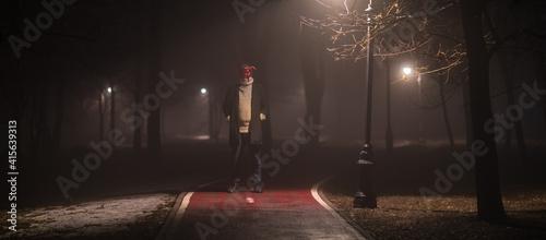 Fototapeta devil masked man in forest at night in fog obraz