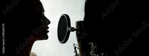 Canvas Print Silhouette of a woman with studio microphone