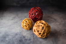 Three Colored Wicker Balls Placed Front To Back On A Concrete Surface With Pinned Focus