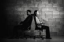 Bad Relationship Concept. Man And Woman In Disagreement. Young Couple After A Quarrel Sitting On Chairs Back To Back. Businessmen And Partners Did Not Share Anything. Low Key. Selective Focus.