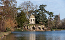 """Romantic Winter View Of The Temple Of Love And The Artificial Grotto On The Isle De Reuilly Located On The Lac Daumesnil In The Largest Parisian Public Park """"Bois De Vincennes""""."""