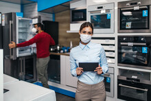 Young Saleswoman Working In Store With Household Appliances. She Is Wearing Face Protective Mask And Holding Tablet. Pandemia, Covid-19 Concept.