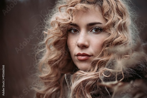 Close-up portrait of a young woman with blonde curly hair