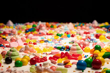 Confectioner's Close Up Of Jelly Beans, Colorful Chocolate Coated Candy, Various Flavours Mixed Sweets, Marshmallow, Snack, Caramels, Swirls, Sugar And Cake Sprinkles. Candy Land Explosion Dream.