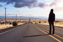 Man Is Standing In The Middle Of The Long Road. Colorful Sunset Sky Art Render. Taken In Oregon, North America.