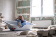 canvas print picture - Renovation apartment. Creative story young happy woman sits in bathtub in the middle of the room. Empty walls, repairs house with their own hands.