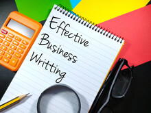 Selective Focus.Word EFFECTIVE BUSINESS WRITTING On Notebook With Penci,glasses And Calculator With Colorful Paper And Black Background.Business Concept.