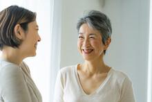 笑顔で会話する30代日本人女性とシニア女性